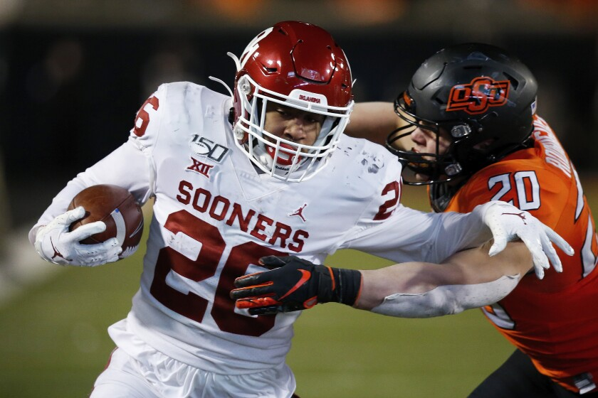 FILE - Oklahoma running back Kennedy Brooks (26) tries to get past Oklahoma State safety Malcolm Rodriguez (20) in the second half of an NCAA college football game in Stillwater, Okla., in this Saturday, Nov. 30, 2019, file photo. Kennedy Brooks returns after sitting out last season with COVID-19 concerns. He's vaccinated now, and ready to roll. (AP Photo/Sue Ogrocki, File)