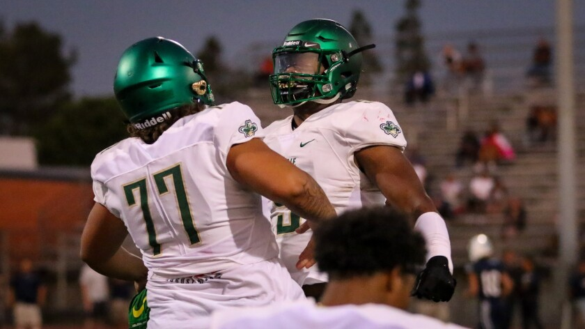 Jordan Banks bumps chests with Narbonne teammate Ikani Tuiono just before kickoff against St. Paul on Sept. 6.