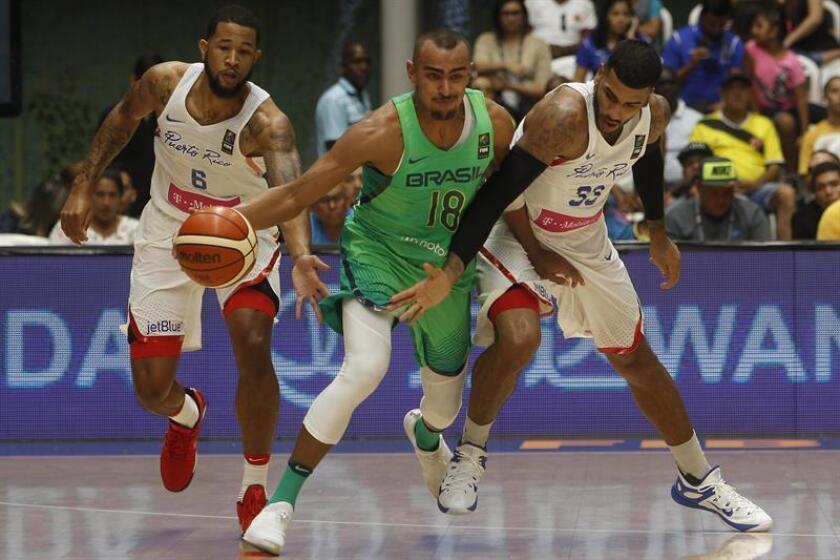 El jugador de la selección brasileña de baloncesto Jimmy Oliveira (c) disputa el balón con Christopher Ortiz (i) y Christopher Gastón (d) de Puerto Rico. EFE/Archivo