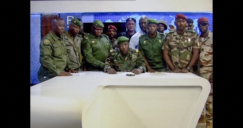 In this image made from video, an unnamed military officer identifying himself as the spokesperson of the National Committee for Rally and Development (CNRD), surrounded by others, makes an address to the nation from state television headquarters in the capital Conakry, Guinea Sunday, Sept. 5, 2021. Mutinous soldiers in the West African nation detained President Alpha Conde on Sunday after hours of heavy gunfire rang out near the presidential palace in the capital, then announced on state television that the government had been dissolved in an apparent coup d'etat. (Radio Television Guineenne via AP)