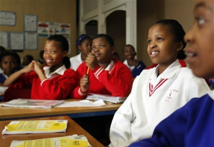 In this Oct. 28, 2010 photo, Samantha Zulu, second from right, looks on as teacher Micheal Mpubane, unseen, speaks during the Bible study class at the Progressive Primary in Johannesburg. Progressive Primary is among an increasing number of such schools for poor South Africans underserved by a gove