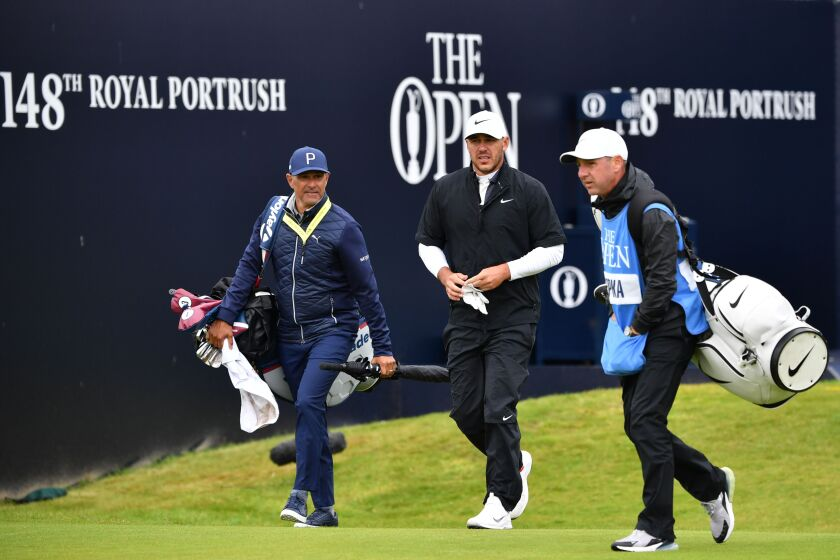 Brooks Koepka, center, and caddie Ricky Elliott, right, head down a fairway during a practice round at Portrush Golf Club on July 17, 2019.