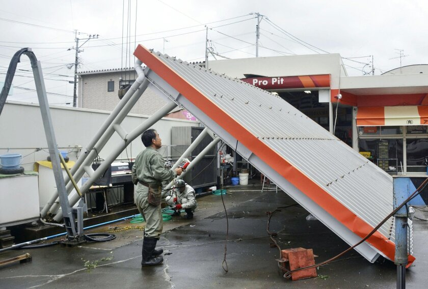 The roof of a car wash topples at a gas station after Typhoon Goni hit Amakusa, Kumamoto prefecture, southwestern Japan, Tuesday, Aug. 25, 2015. The powerful typhoon damaged buildings, tossed around cars and flooded streets in southwestern Japan on Tuesday before heading out to the Sea of Japan. (AP Photo/Kyodo News via AP) JAPAN OUT, MANDATORY CREDIT
