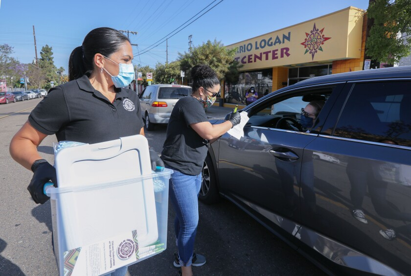 Lodia Ruiz, middle, of the YMCA, speaks to essential worker Carman Padilla on May 2 as she arrives in her vehicle in front front of the Chicano Federation's Barrio Logan Child Development Center to receive cleaning supplies and a sanitation kit from Chicano Federation of San Diego CEO, at left.