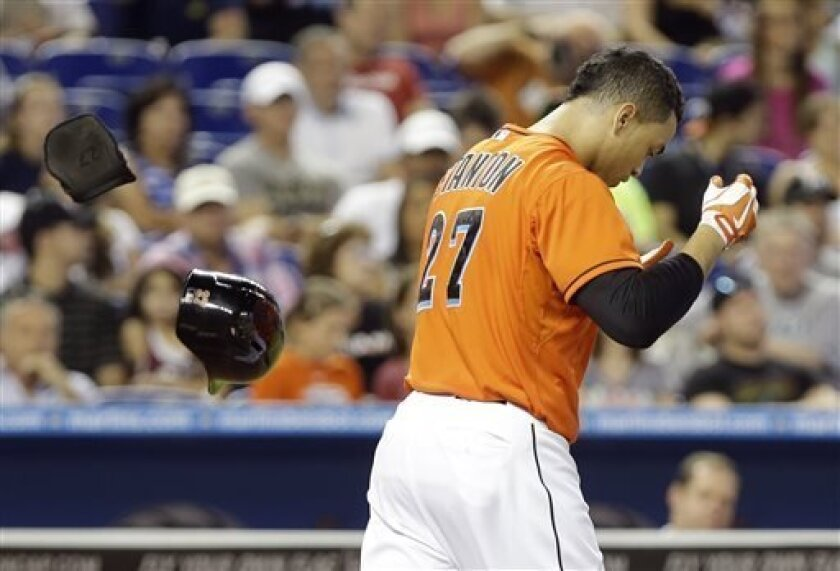 Miami Marlins' Giancarlo Stanton tosses his helmet after striking out in the eighth inning during an interleague baseball game against the Cleveland Indians, Sunday, Aug. 4, 2013, in Miami. The Indians defeated the Marlins 2-0. (AP Photo/Lynne Sladky)