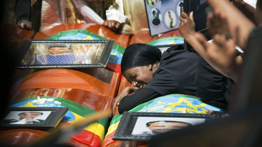 Relatives grieve next to empty caskets draped with the national flag at a mass funeral at the Holy T