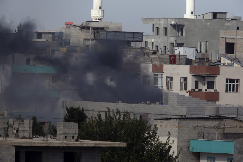 """Smoke from a fire caused by an incoming mortar fired from the Syrian side, billows in Akcakale, Sanliurfa province, southeastern Turkey, Thursday, Oct. 10, 2019. Turkey's foreign minister says Turkish troops intend to move some 30 kilometers (19 miles) deep into northern Syria and that its operation will last until all """"terrorists are neutralized,"""" a reference to Syrian Kurdish fighters. (AP Photo/Cavit Ozgul)"""