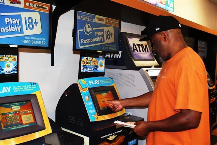Un hombre compra billetes del Powerball en un puesto de venta de lotería. EFE/Archivo