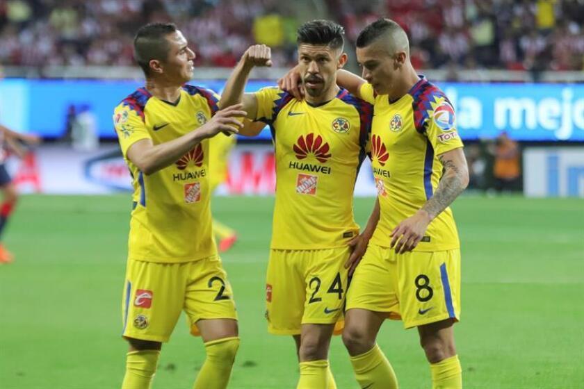 El jugador de América Oribe Peralta (c) celebra la anotación de un gol con su compañero Mateus Uribe (d) y Paul Aguilar (i). EFE