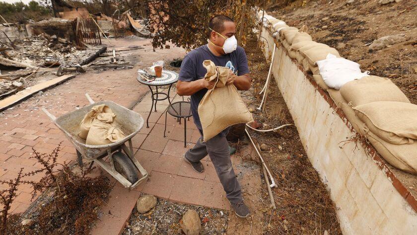 MALIBU, CA - NOVEMBER 19, 2018. Jonathan Lopez loads sandbags to help Victor Lobl, to protect agains