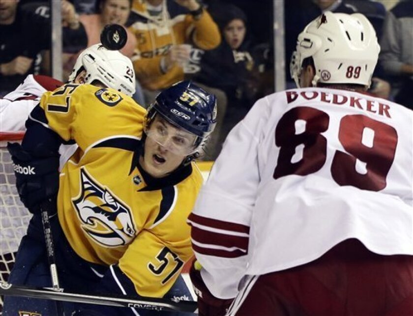 Nashville Predators left wing Gabriel Bourque (57) and Phoenix Coyotes right wing Mikkel Boedker (89), of Denmark, watch a rebound bounce by in the second period of an NHL hockey game, Thursday, Feb. 14, 2013, in Nashville, Tenn. (AP Photo/Mark Humphrey)