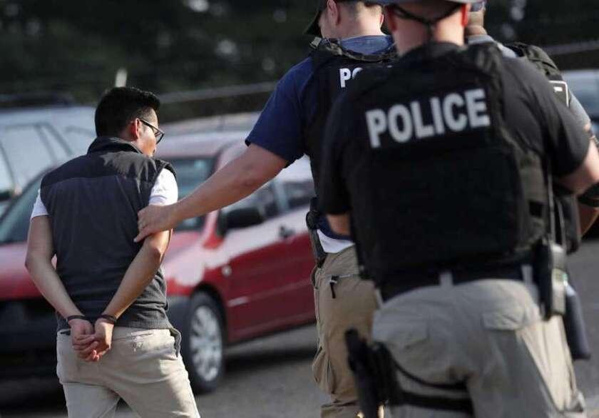 La policía detiene a un individuo en la planta Koch Foods de Morton, Mississippi. Los trabajadores sin premiso de residencia son detenidos y deportados, pero quienes los contratan rara vez deben rendir cuentes.