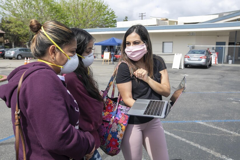 Resource teacher Juana Lopez (right) helps eighth-grade student Josalyn Huerta (center) with some software instruction in the parking lot at Del Dios Arts and Science Academy, an Escondido middle school, on Friday. Josalyn's mother Araceli Garcia is at left.