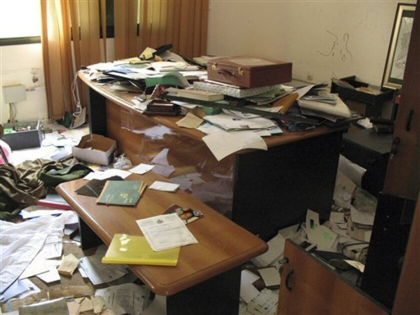 This Sunday, Sept. 4, 2011 photo shows an ransacked desk in Moammar Gadhafi's intelligence headquarters in Tripoli, Libya. Hundreds intelligence documents seen by The Associated Press in Tripoli show how Gadhafi's authoritarian regime using all its means failed to quash an armed rebellion largely fueled by hatred of its tools of control. (AP Photo/Ben Hubbard)
