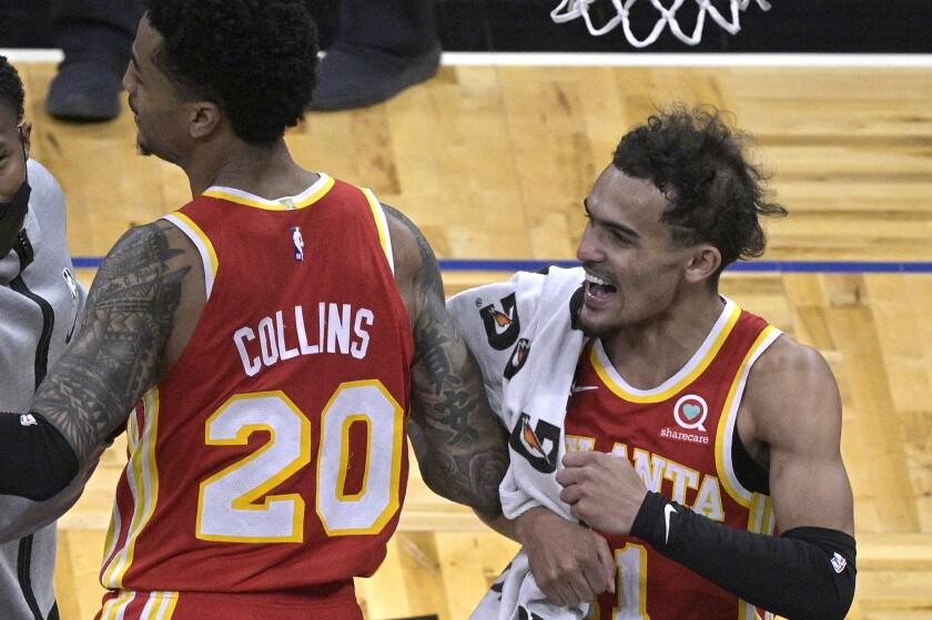 Atlanta Hawks forward John Collins (20) and guard Trae Young, right, celebrate the team's win over the Orlando Magic in an NBA basketball game Wednesday, March 3, 2021, in Orlando, Fla. (AP Photo/Phelan M. Ebenhack)