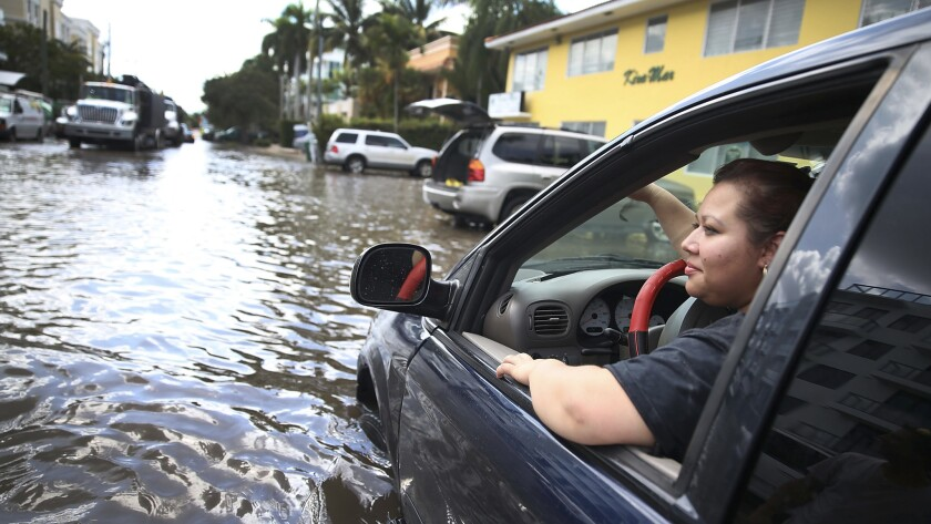 Sandy Garcia sits in her vehicle on a flooded street in Fort Lauderdale, Florida, in 2015.