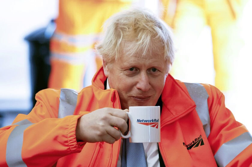 Britain's Prime Minister Boris Johnson holds a mug, during a visit to a construction site in Manchester, England, Monday, Oct. 4, 2021. (Phil Noble/PA via AP)