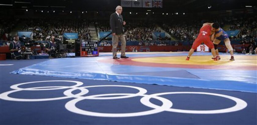 FILE - The Aug. 5, 2012 file photo shows Cuba's Gustavo Balart, left, competing with South Korea's Choi Gyu-jin during 55-kg Greco-Roman wrestling competition at the 2012 Summer Olympics in London. IOC leaders have dropped wrestling for the 2020 Games in a surprise decision to scrap one of the olde