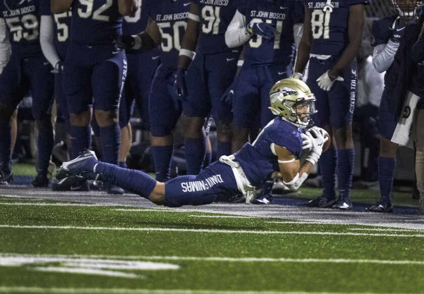 A St. John Bosco player tries to make a diving catch.