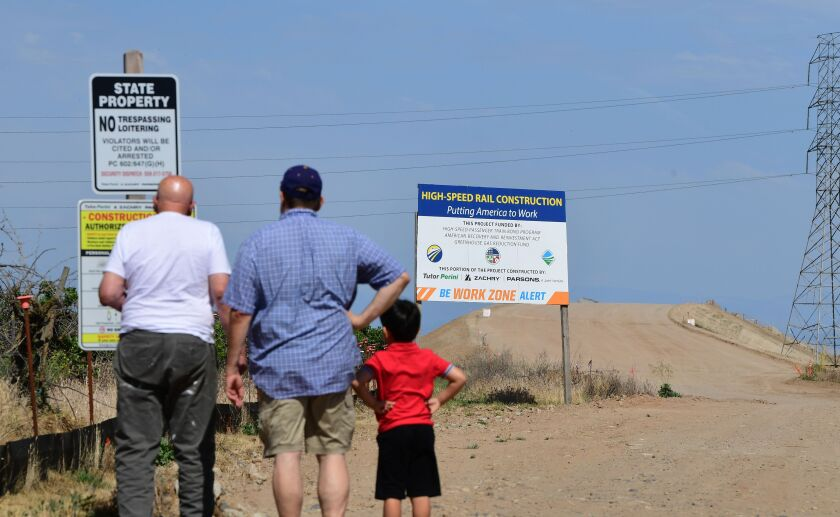 People read signs near a constuction site off Avenue 12 in Madera, California.