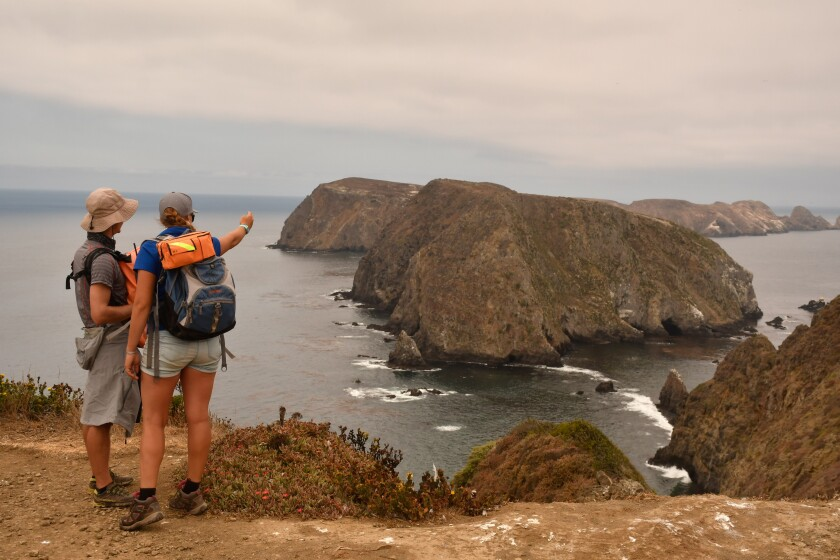 Hikers on Anacapa Island look from Inspiration Point to the island's central and western islets.