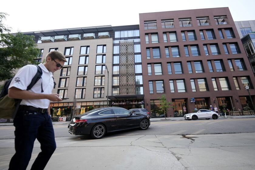 Una persona camina frente al Hotel Maven en el centro de Denver, el 11 de julio de 2021.