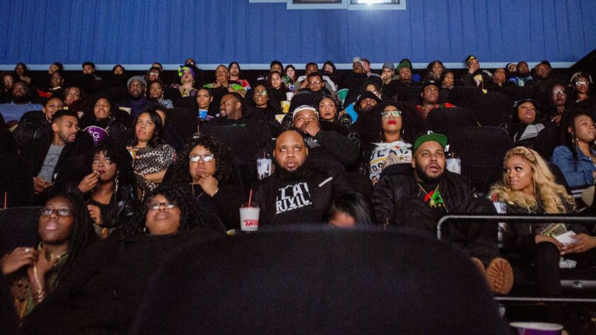"Audience members watch the beginning of ""Black Panther"" during a private screening on Friday, Feb. 1"