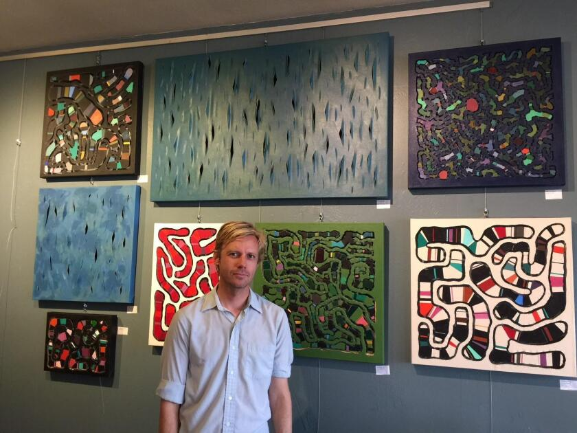 Aaron Garretson with his work on exhibit at Bird Rock Coffee Roasters through the month of October 2018.