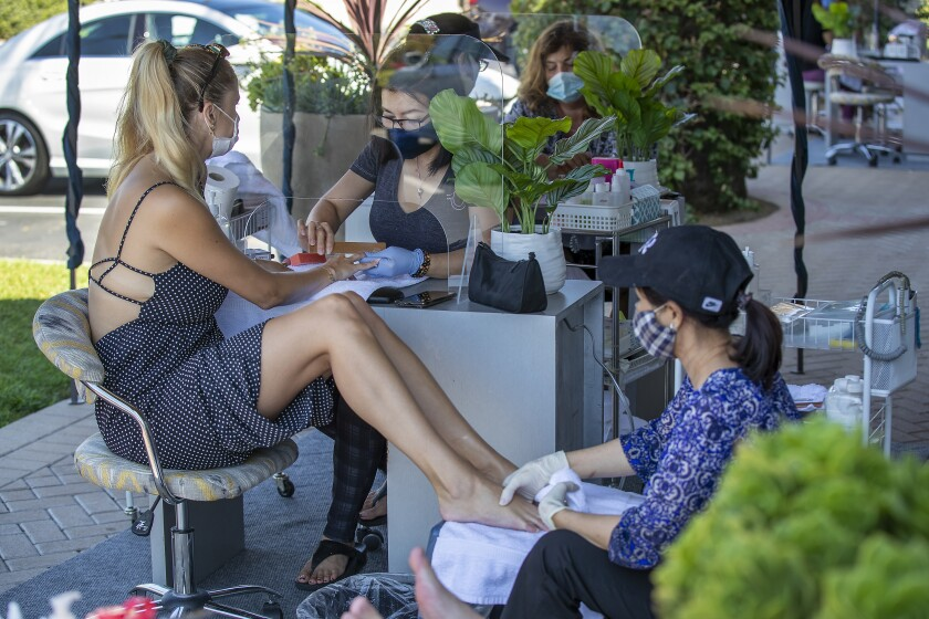 Beauty technicians wear face masks as they give clients wearing face masks manicures and pedicures outdoors in Tustin.