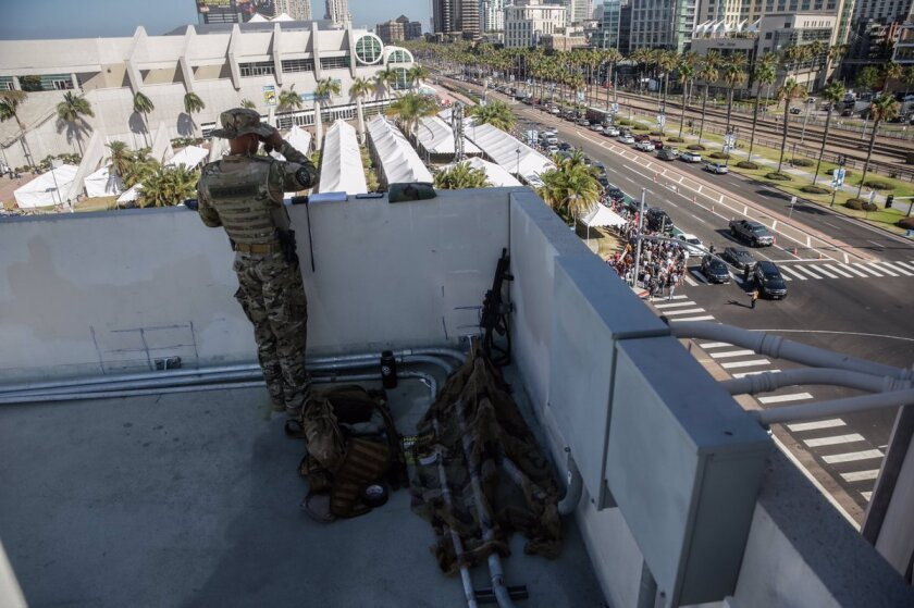 San Diego Police Officer Tito Santos stands at the top of the Hilton San Diego Bayfront parking structure, surveying the surrounding area with binoculars, rifle at his side.