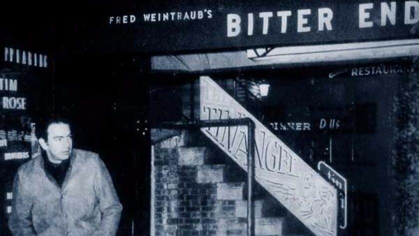 Neil Diamond standing in front of the Bitter End in New York City.