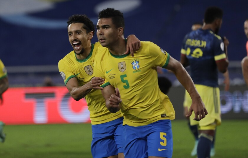 Brazil's Casemiro, right, celebrates with teammate Marquinhos after scoring his side's 2nd goal against Colombia during a Copa America soccer match at Nilton Santos stadium in Rio de Janeiro, Brazil, Wednesday, June 23, 2021. (AP Photo/Silvia Izquierdo)