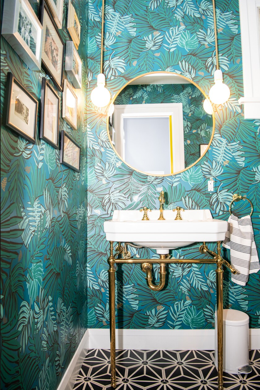 A salon wall in the powder room. The blue leaf-covered wallpaper is by Justina Blakeney.