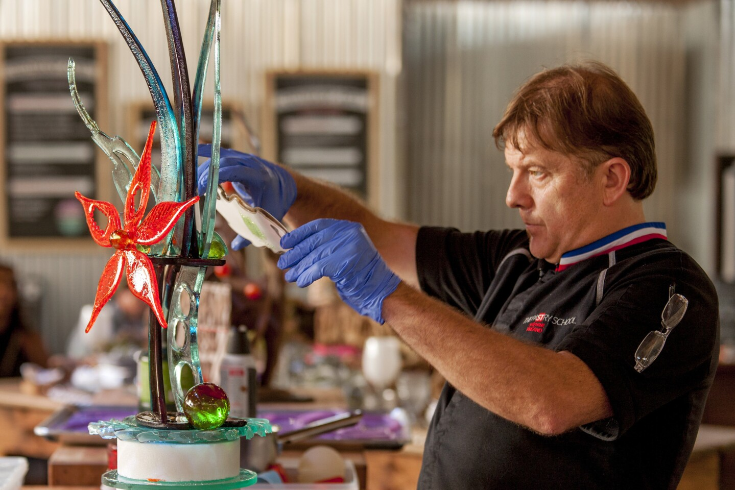 Pastry chef and master chocolatier Stephane Treand mounts a molded piece onto the sugar sculpture he created Sunday evening at the Orange County Fair.