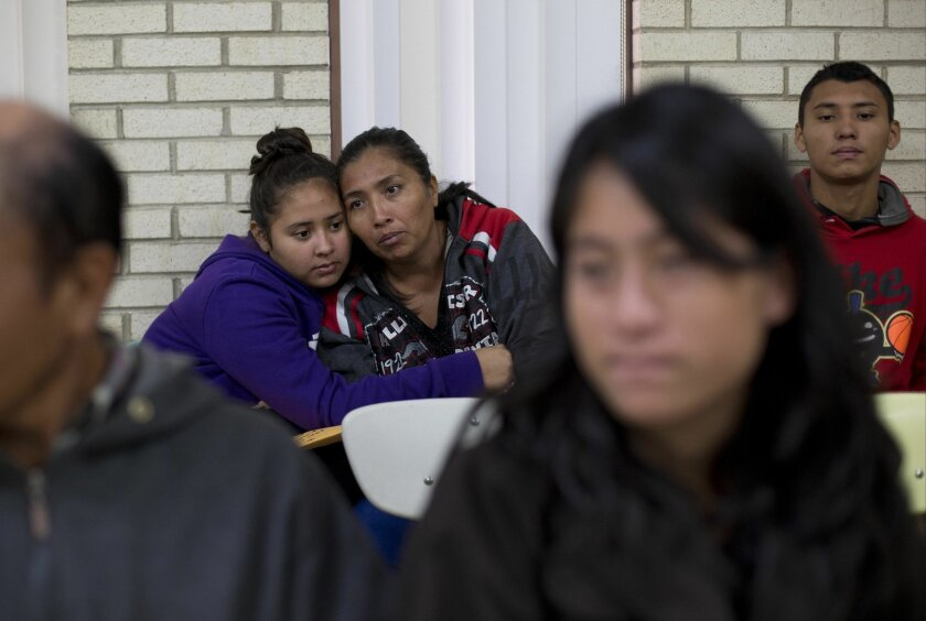 Central American migrants embrace as they wait for assistance at a center for newly-arrived migrant families with children, at Sacred Heart Catholic Church in McAllen, Texas.
