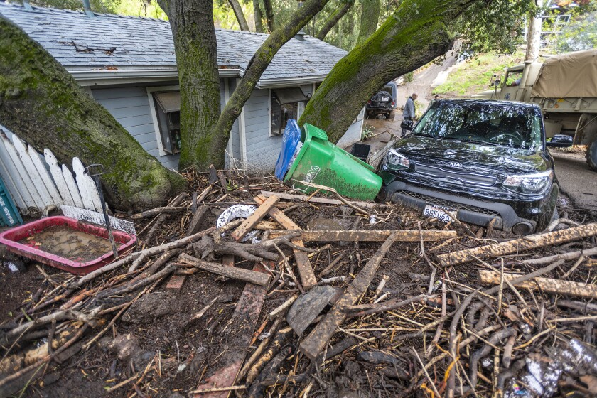 Mud, branches and and other debris are piled in front of a home in Silverado Canyon in Silverado, Calif., after heavy rain caused flash flooding and mudslides earlier Wednesday, March 10, 2021. (Mark Rightmire/The Orange County Register via AP)