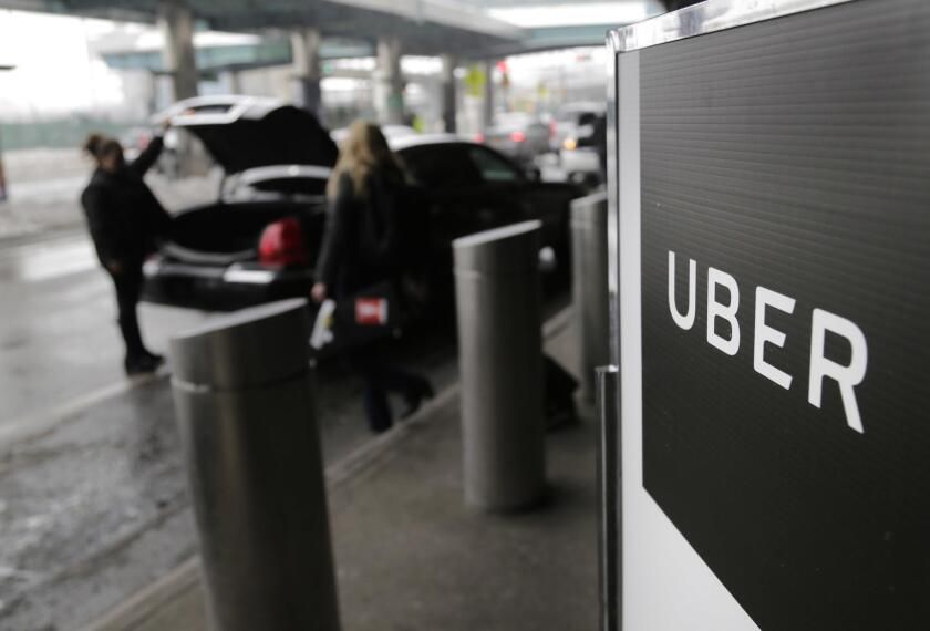 A sign marks a pick-up point for Uber vehicles at LaGuardia Airport in New York in this March 15, 2017, photo. The ride-sharing company is slated to announce significant changes to its culture and management on June 13, 2017.