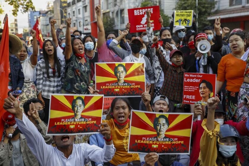 Demonstrators hold signs bearing the image of deposed Myanmar leader Aung San Suu Kyi