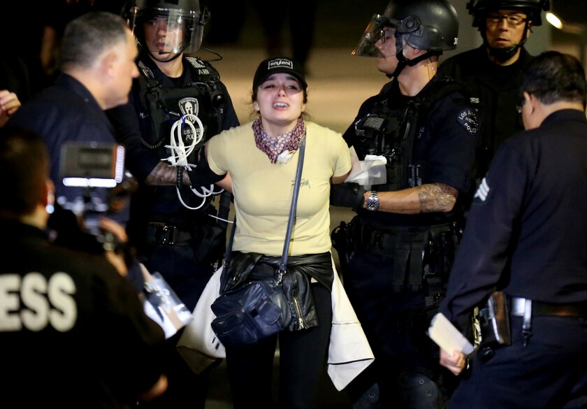 Police arrest an anti-Trump protester in the early morning hours Saturday. The LAPD arrested about 150 people at Grand Park after a night of marching through downtown L.A.