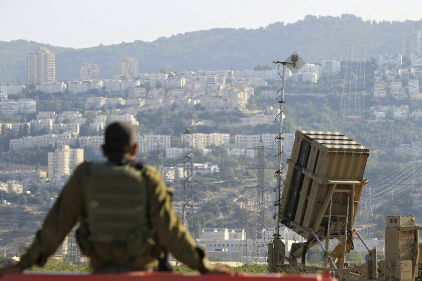 """FILE - In this Aug. 28, 2013 file photo, an Israeli soldier is seen next to an Iron Dome rocket interceptor battery deployed near the northern Israeli city of Haifa. A state-owned Israeli arms company said it will unveil a new laser-defense system called the """"Iron Beam."""" The system is to be display"""