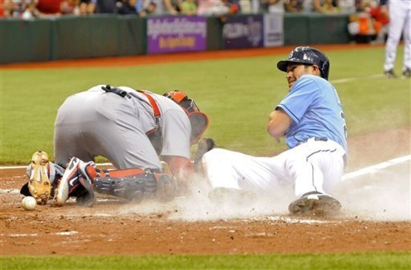 Tampa Bay Rays Johnny Damon, right, slides safely home in front of St. Louis Cardinals catcher Yadier Molina, left, after hitting a double, advancing to third base on the throw and home on the error during the sixth inning of a baseball game Sunday, July 3, 2011, in St. Petersburg, Fla. (AP Photo/Brian Blanco)