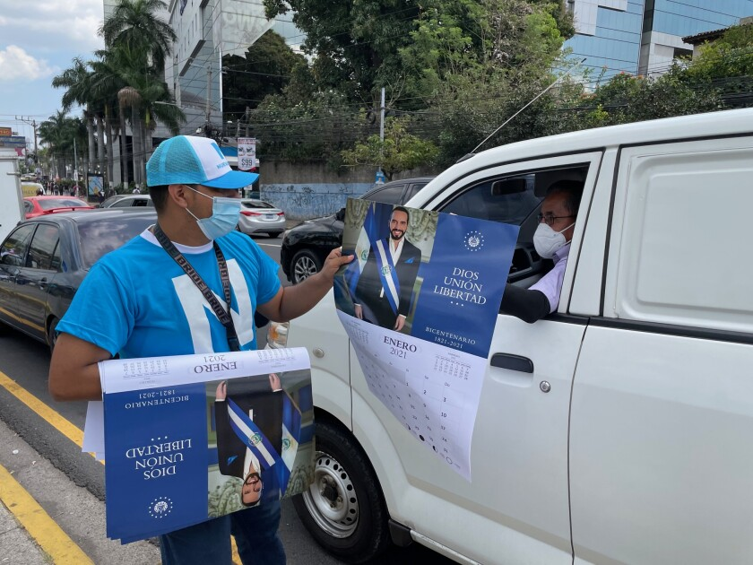 A man hands political literature to a motorist