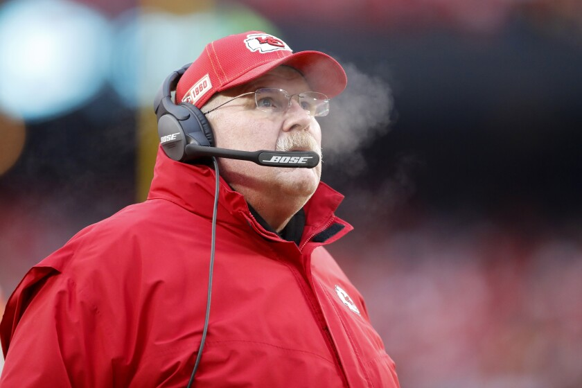 Chiefs coach Andy Reid checks the scoreboard during the first half of an NFL divisional playoff football game against the Texans.