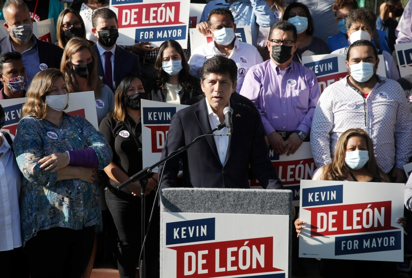 Los Angeles City Councilman Kevin de León speaks at a microphone, backed by masked supporters.