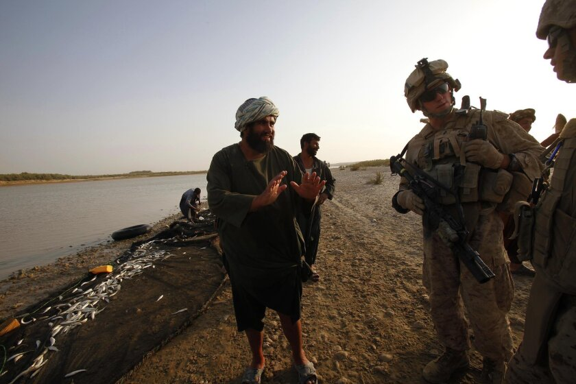 During his squad patrol, Marine Sgt. David McFadden questions Afghan fishermen along the Helmand River.