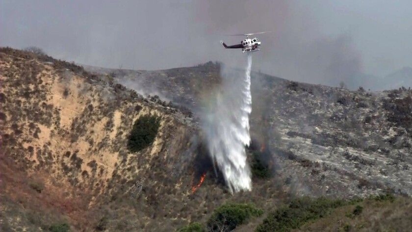 A helicopter drops water on a 50-acre brush fire that broke out in Ventura on Monday. It was contained by nightfall.