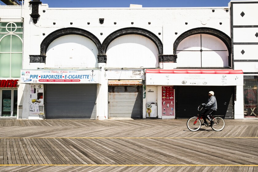 A cyclist rides past shuttered businesses during the coronavirus outbreak on the boardwalk in Atlantic City, N.J.