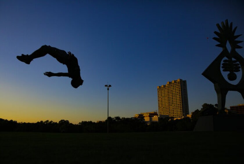 In this Tuesday, Sept. 24, 2019 photo, Marcellus Hunt, 18, of Spring, Texas, practices his flips at Hermann Park in Houston as the sun sets. The sunsets in the Houston area have had a purple haze to them, caused by a volcanic eruption in Russia months ago. Meteorologist Jimmy Fowler, with the National Weather Office in Galveston, said that the particles causing people to see purple light rays are sulfur dioxide gas. (Elizabeth Conley/Houston Chronicle via AP)