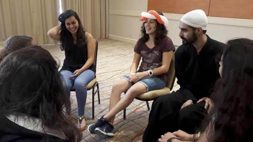 Daniel Halabi, 22, a sheikh or religious leader in the Druze faith, leads a discussion with Carmen Masri, left, and Luna Masri at the American Druze Society conference in Irvine in July.