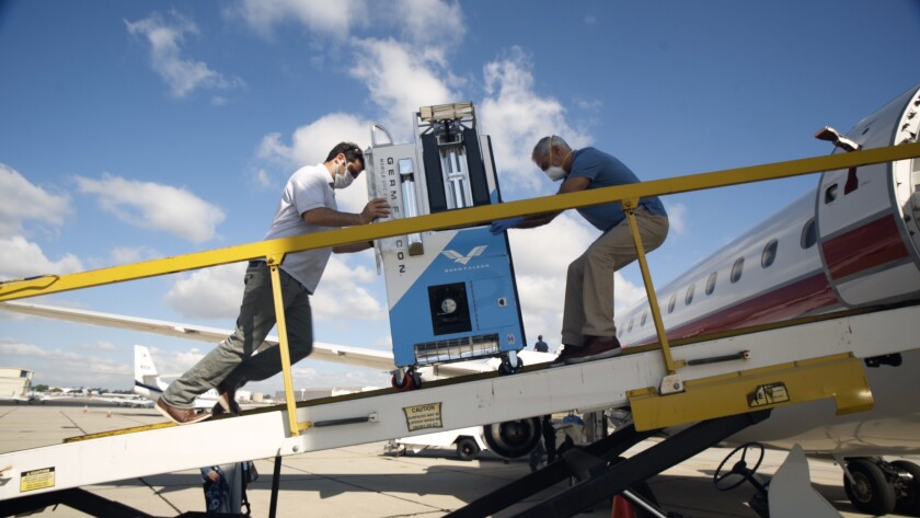 Elliot and Arthur Kreitenberg push the GermFalcon on a plane to disinfect the cabin.